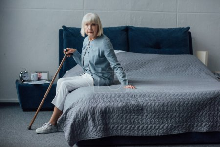 Photo for Senior woman sitting on bed with walking stick at home and looking at camera - Royalty Free Image