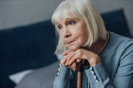 Photo for Portrait of thoughtful senior woman with hands on walking stick sitting on bed at home - Royalty Free Image