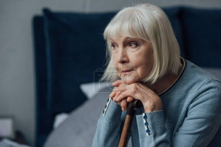 Photo for Thoughtful senior woman with hands on walking stick sitting on bed at home - Royalty Free Image