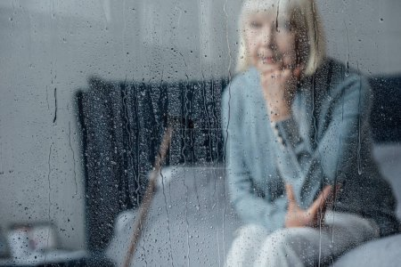 Photo for Lonely senior woman sitting on bed and propping chin with hand at home through window with raindrops - Royalty Free Image