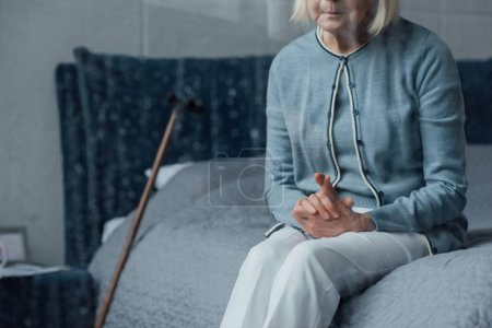Photo pour Vue partielle de haute femme assise sur le lit avec les mains jointes à la maison - image libre de droit