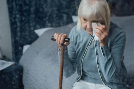 senior woman sitting on bed, holding walking stick and wiping tears with handkerchief at home
