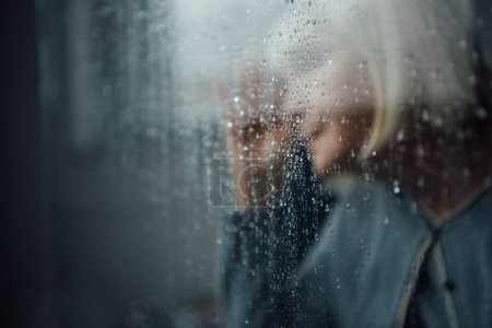 Photo for Blurred portrait of lonely senior woman at home through window with raindrops - Royalty Free Image