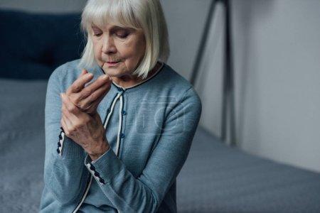 Photo pour Haute femme assis sur le lit et la mesure des impulsions avec la main à la maison - image libre de droit