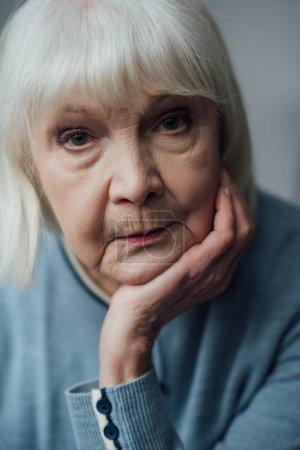 Photo pour Portrait de femme senior triste étaiement menton avec la main et en regardant la caméra - image libre de droit