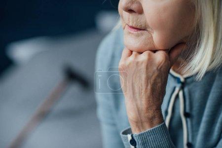 Photo pour Vue recadrée de la femme âgée appui menton avec la main à la maison - image libre de droit