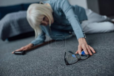 Photo for Lonely senior woman lying on floor, feeling unwell and reaching for glasses at home - Royalty Free Image