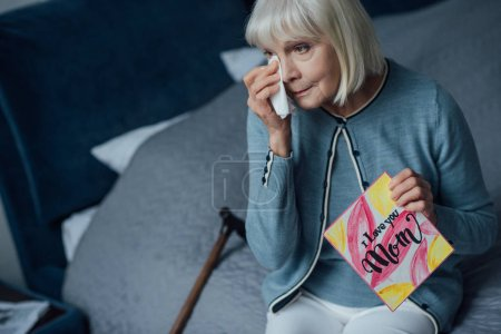 Photo for Sad senior woman holding card with 'i love you mom' lettering, crying and wiping tears with handkerchief at home - Royalty Free Image