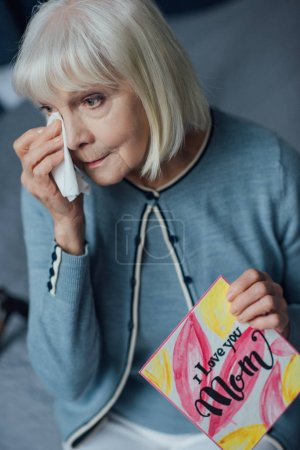 senior woman holding card with 'i love you mom' lettering, crying and wiping tears with handkerchief at home