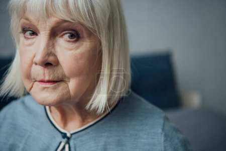 portrait of upset senior woman looking at camera at home