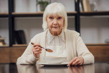 sad senior woman sitting at table, looking at camera and eating at home