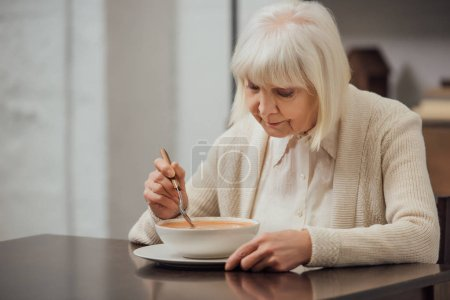 Photo pour Haute femme avec des cheveux gris assis à table et manger une soupe crème à la maison - image libre de droit