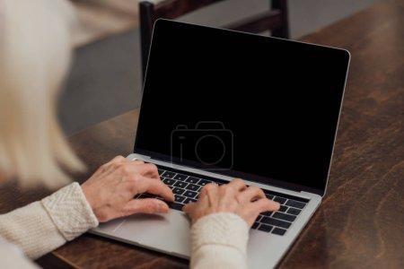 Photo pour Vue recadrée de la femme âgée assise à la table et tapant sur un ordinateur portable avec écran blanc à la maison - image libre de droit