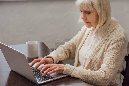 Photo pour Haute femme assis à table et en tapant sur l'ordinateur portable à la maison - image libre de droit