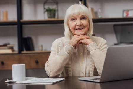 Photo for Smiling senior woman sitting at table with laptop, looking at camera and propping chin with hands at home - Royalty Free Image