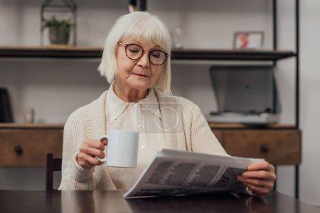Photo pour Haute femme à lunettes, assis à table, de boire du café et de lire le journal à la maison - image libre de droit