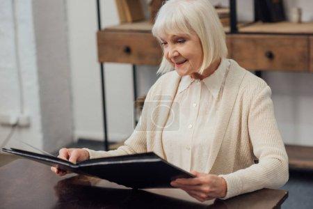 Photo pour Femme senior souriante assis à table et en regardant d'album photo à la maison - image libre de droit