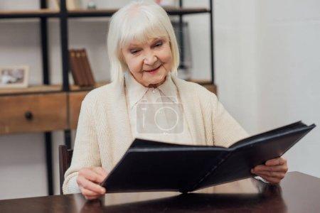 Photo pour Femme senior souriante aux cheveux gris, assis à table et en regardant d'album photo à la maison - image libre de droit