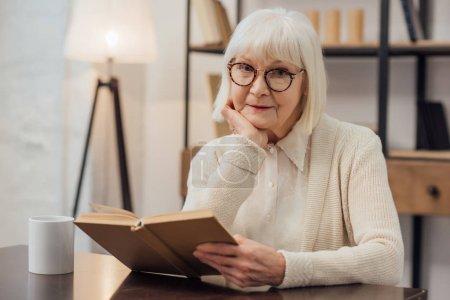 Photo pour Haute femme à lunettes assis à table, étaiement menton avec la main et lecture de livre à la maison - image libre de droit