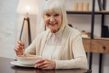 Photo pour Femme senior souriante assis à table et manger une soupe crème à la maison - image libre de droit