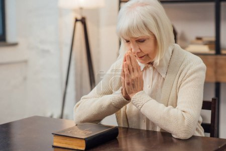 Photo for Concentrated senior woman sitting and praying in front of holy bible at home - Royalty Free Image