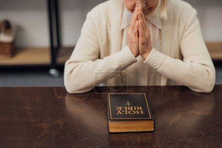 Photo for Cropped view of senior woman sitting and praying in front of holy bible at home - Royalty Free Image