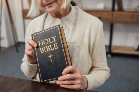 Photo for Cropped view of senior woman holding holy bible at home - Royalty Free Image