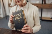 cropped view of senior woman holding holy bible at home