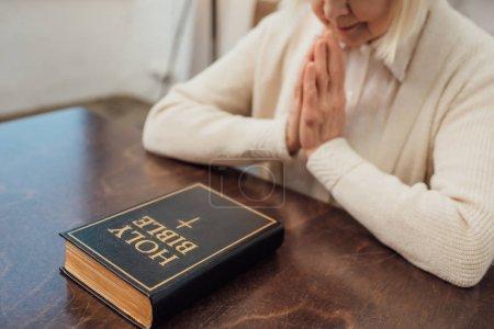 Teilansicht einer Seniorin, die zu Hause vor der Heiligen Bibel sitzt und betet