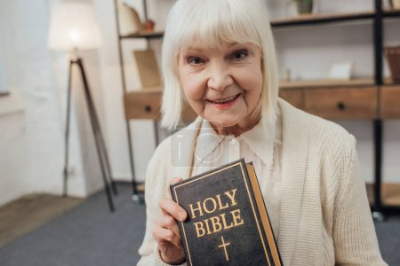 Photo for Smiling senior woman looking at camera and holding holy bible at home - Royalty Free Image