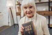 smiling senior woman looking at camera and holding holy bible at home