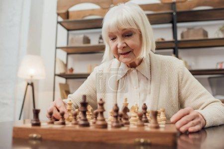 Photo pour Haute femme avec des cheveux gris assis à table et jouer aux échecs à la maison - image libre de droit