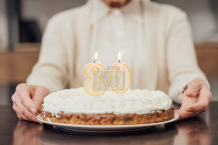 Photo for Partial view of senior woman holding  birthday cake with number 80 on top at home - Royalty Free Image