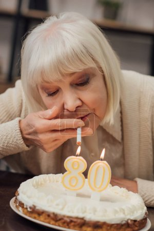 senior woman lighting up cigarette from burning candles on birthday cake at home