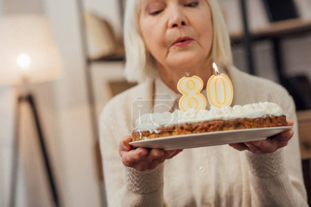 senior woman blowing out candles on cake with number 80 on top while celebrating birthday at home