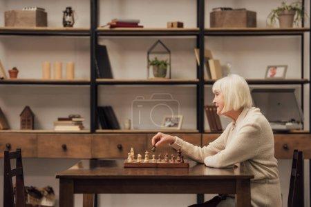 Selektiver Fokus der Seniorin, die am Tisch sitzt und im Wohnzimmer Schach spielt