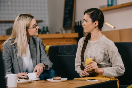 beautiful woman chatting with friend while holding drink in cafe