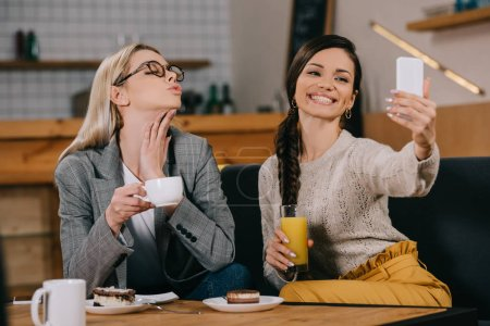 cheerful women taking selfie and holding drinks in cafe