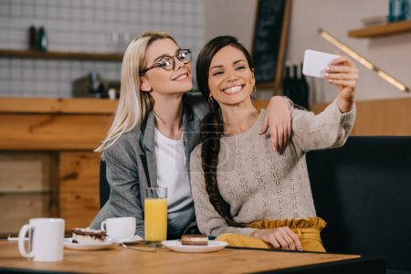 happy women smiling while taking selfie in cafe