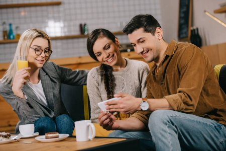 handsome man holding smartphone near attractive women in cafe