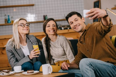 handsome man taking selfie with female friends in cafe