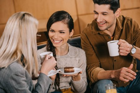 cheerful woman chatting  with friends while holding cake in cafe