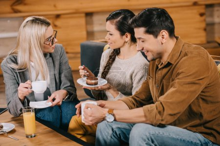 smiling woman chatting with friends while holding cake in cafe