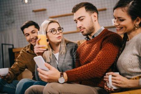 Photo pour Groupe joyeux d'amis regardant smartphone tout en tenant des boissons - image libre de droit