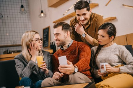 surprised woman looking at man holding smartphone near friends