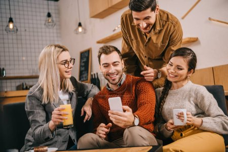 handsome man pointing with finger at smartphone near friends