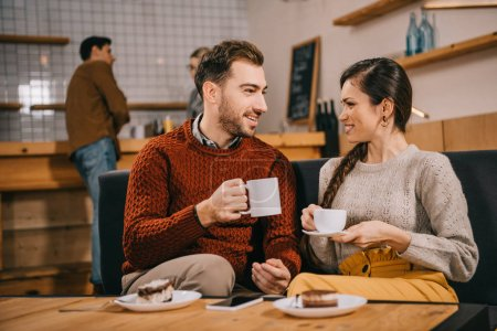 selective focus of couple holding cups and chatting in cafe