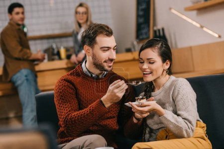 selective focus of handsome man feeding attractive woman with cake in cafe