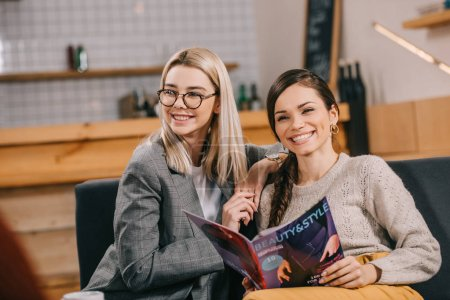 attractive woman holding beauty magazine and smiling near friend in glasses