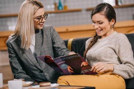 Photo pour Attrayant femme dans des lunettes regarder ami lecture beauté magazine - image libre de droit